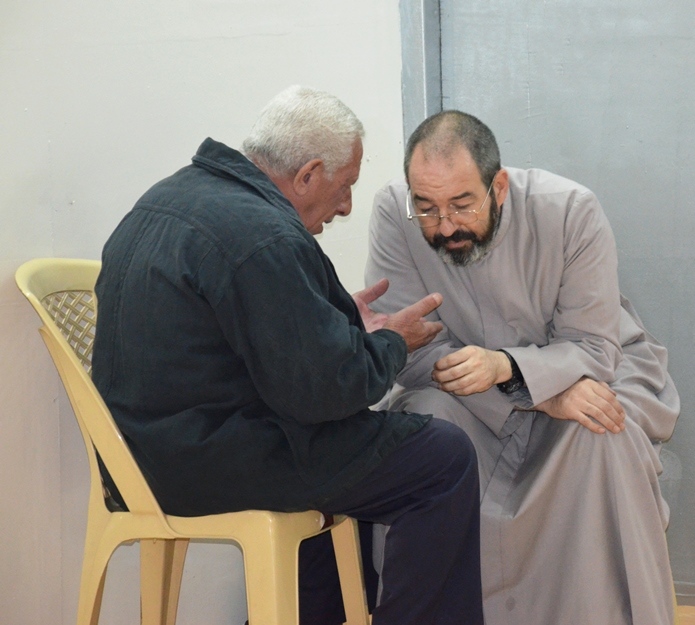 Father Luis Montes hears confession in the back of the new c
